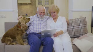 Old married couple uses tablet at home sitting on sofa