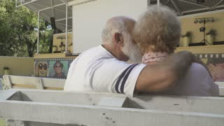 Old people are kissing in summer cinema