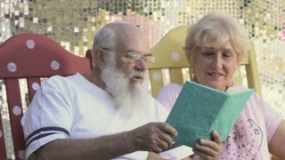 Old people reads book in rocking chairs, the husband kiss a wife in a cheek