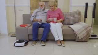 Old people relax at sofa during vacuum cleaner clean the floor in living room