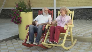 Old people swings in rocking chair and eats popcorn