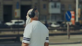 Old sporty man listens to the music