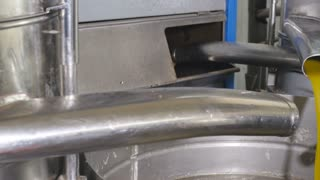 Olive oil flows out of the pipe on an oil factory