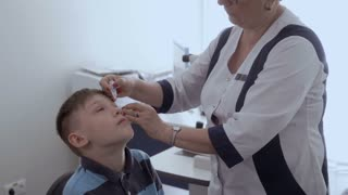 Ophthalmologist drip drops into the eyes of little boy