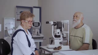 Ophthalmologist talk with old patient after checking his vision