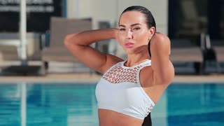 Passionate young woman touches her wet hair in swimming pool