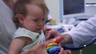 Pediatrician listening the breathing of little girl with stethoscope
