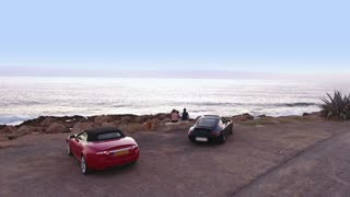 People are relaxing on the coast of the ocean after the traveling on luxury cars