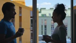 People drinking coffee have a conversation near the window