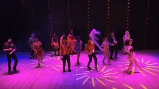 People in bright costumes crazy dancing in colorful lights at modern stage