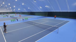 People play tennis at tennis court - view from flying drone