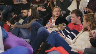 People sit down on the pillow on the floor and watching stand-up show