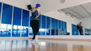 Plastic young woman dancing the hip-hop in front of the mirror in gym
