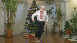 Pleasant old man dances near the christmas tree