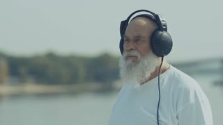 Pleasant old man has a relax listening music with headphones