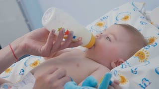 Portrait of adorable boy sucks the mixture from bottle