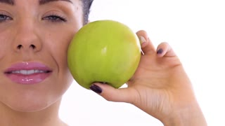 Portrait of beautiful woman with green apple at white background