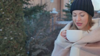 Portrait of cute girl with red lips drinks a hot tea to warm at winter outdoors