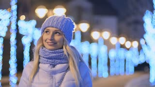 Portrait of cute smiling blonde at night lights background