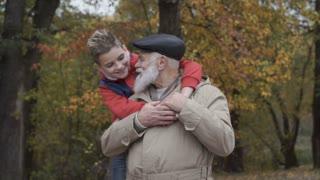 Portrait of grandson embraces grandfather