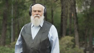 Portrait of gray-haired man listens music with headphones