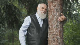 Portrait of handsome senior man hugs a tree trunk