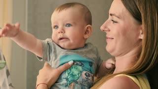 Portrait of happy mother kisses a cute little baby