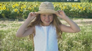 Portrait of little girl in hat grimacing at the sunflowers background