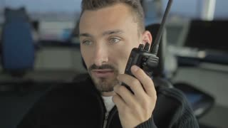 Portrait of man with portable radio in control tower
