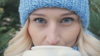 Portrait of pretty blonde drinks a hot tea