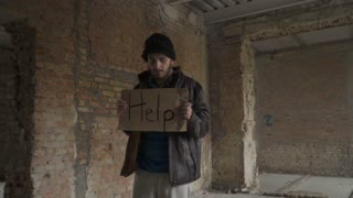 "Portrait of sick dirty homeless with table ""help"