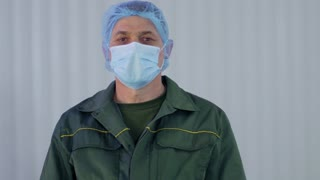 Portrait of worker in uniform removes protective mask from his face