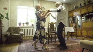 Positive senior couple dancing at home