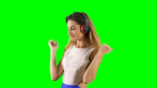 Pretty blonde dancing to music at green background