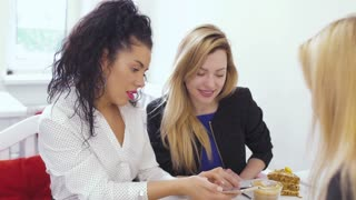 Pretty caucasian women looking at phone and discuss something in cafe