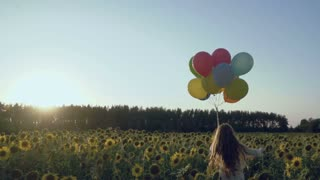 Pretty child runs with balloons at the sunflower field