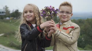 Pretty children give bouquet of flowers