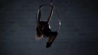 Pretty girl hangs upside down on the aerial hoop