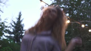 Pretty girl jumps and shakes her hair at the park