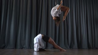 Pretty girl makes a tricks on aerial hoop and her friend warms up on floor