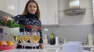 Pretty girl pours champagne into glasses on the kitchen at home