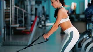 Pretty girl training on simulator in the gym