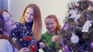Pretty girls decorate Christmas tree