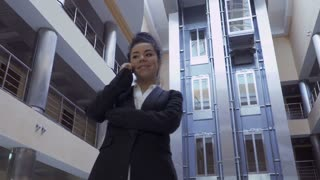 Pretty lady in black suit talks on phone in a hotel