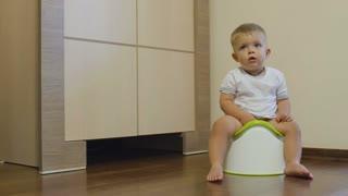 Pretty little boy pisses in his potty