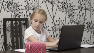 Pretty little girl works with laptop