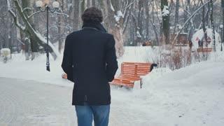 Pretty man walks in the winter park