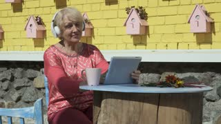 Pretty old woman listens music and uses tablet