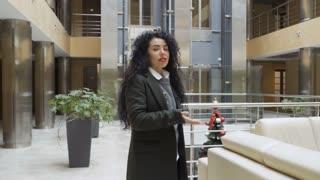 Pretty woman journalist tells something to camera