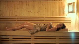 Pretty woman lays on wooden bench and relaxing in the sauna